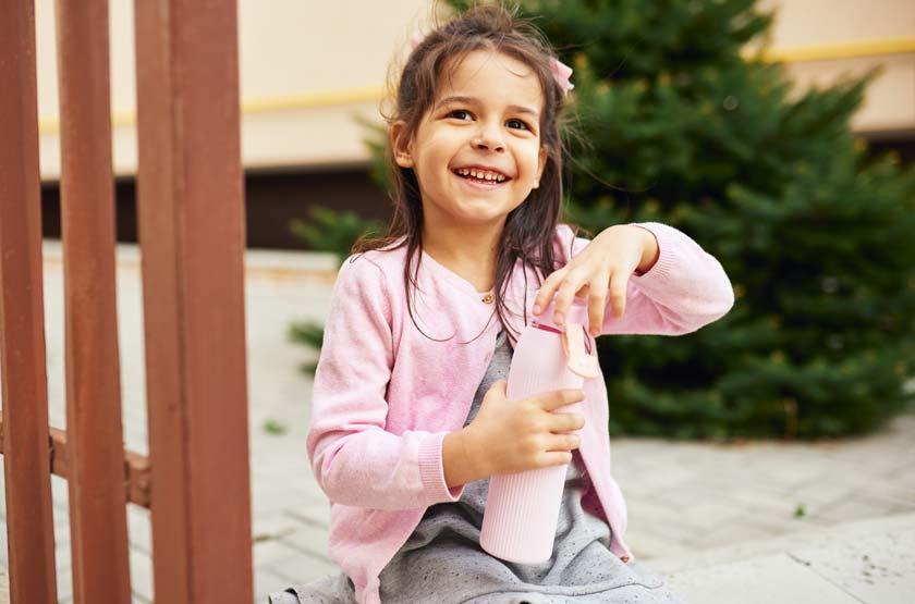 Mädchen mit Glasflasche für Kinder in der Hand