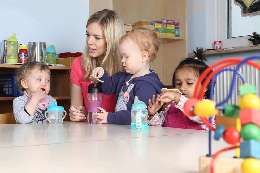 Kinder sitzen mit Erzieherin im Kindergarten am Tisch. Auf dem Tisch stehen Kindergarten Trinkflaschen